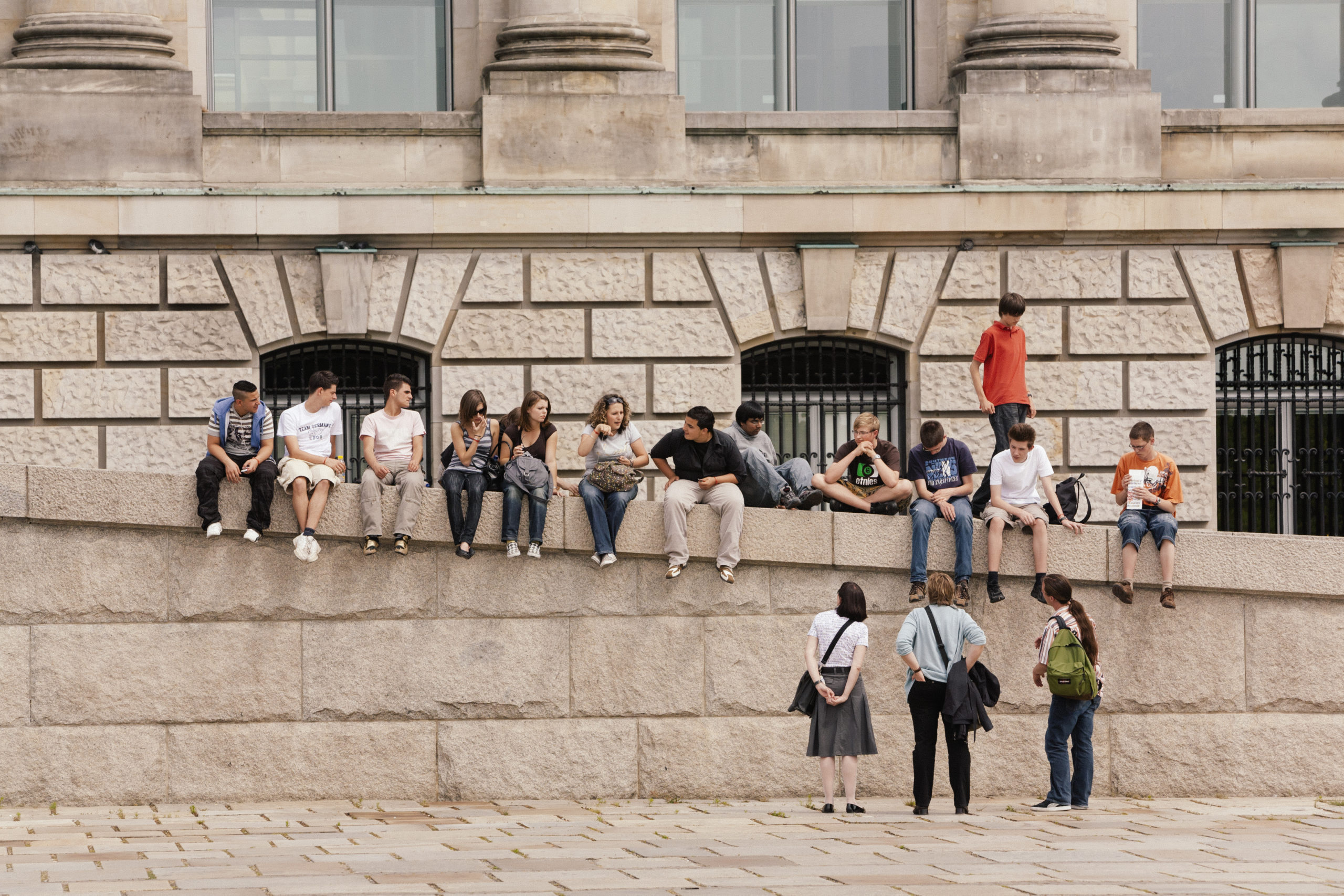 A tour group sitting on the steps at the Reichstag in Berlin, Germany