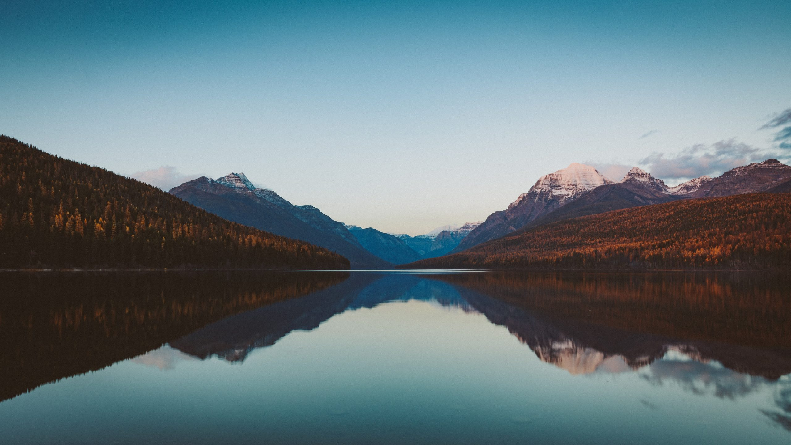The calm waters of Bowman Lake reflect the sky and mountains on a clear fall evening.