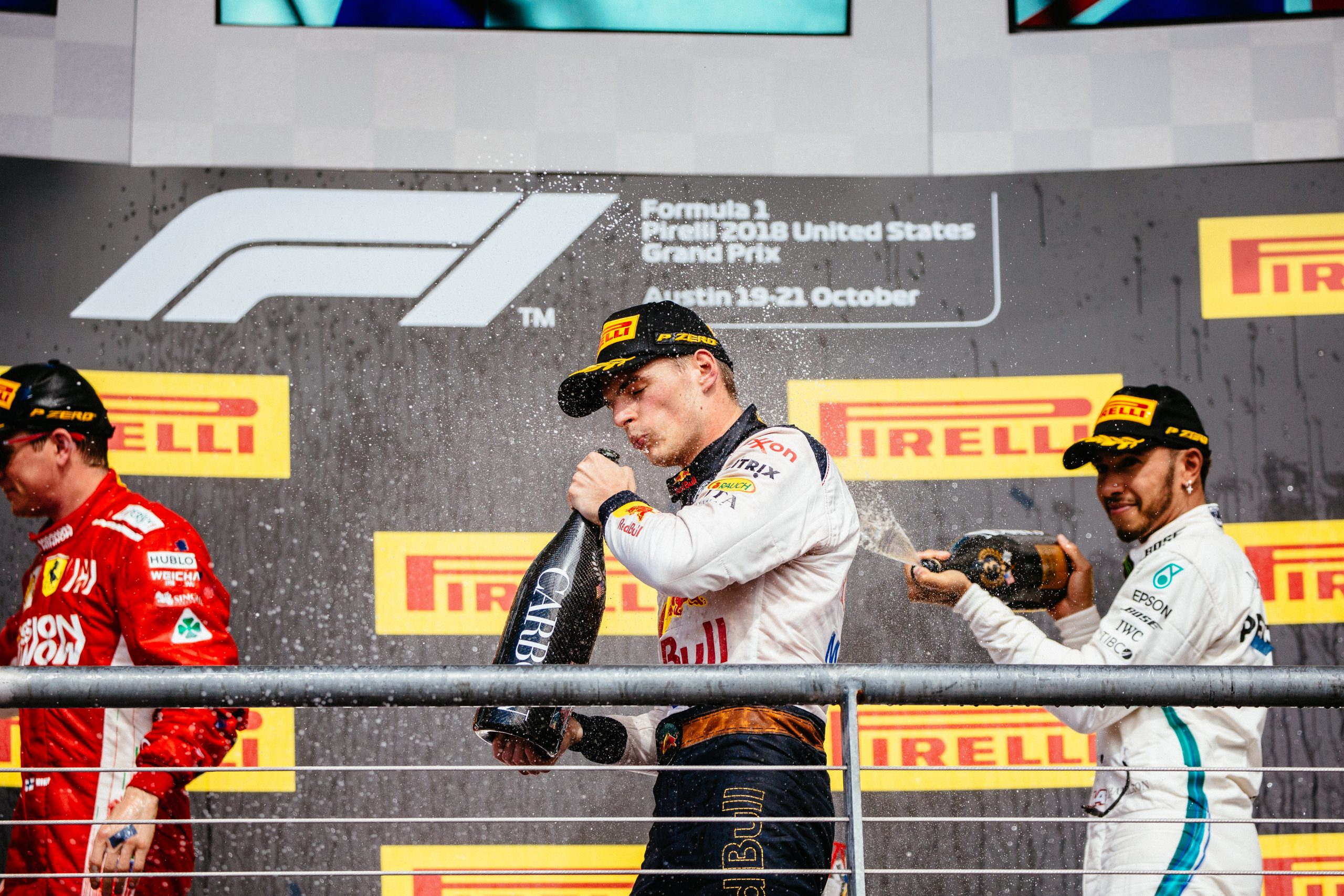 Lews Hamilton spraying Max Verstappen with champaign on the podium